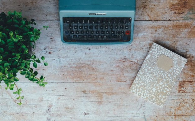 typewriter and notebook for writing blog posts for therapists