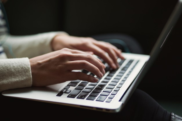 copywriter typing blogs on a computer for therapists